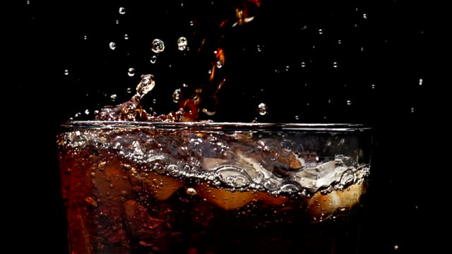 Cola soda pouring into glass of ice with splashes at slow motion on a black background