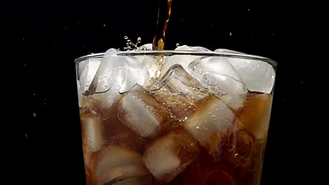 Pouring cola soda into glass of ice with splashes at slow motion on a black background video