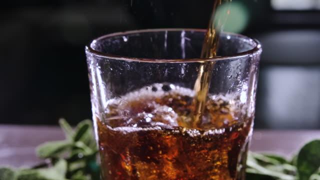 cola con bolle in vetro. una bevanda marrone viene versata in un bicchiere con ghiaccio. cocktail con whisky e rum. bevanda ghiacciata. bere soda gassata. sete di bevande. primo piano. macro. bicchiere con ghiaccio. - rum superalcolico video stock e b–roll