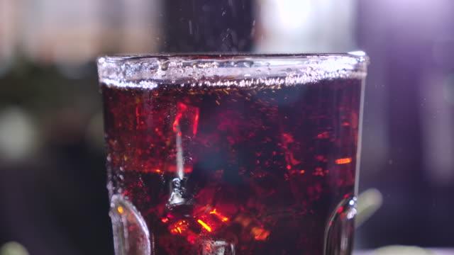 vídeos y material grabado en eventos de stock de cola con burbujas en vidrio. los cubitos de hielo caen en una taza. cóctel con whisky y ron. bebida helada. beber soda carbonatada. bebida para la sed. primer plano. macro. vidrio con hielo. a cámara lenta. - cola gaseosa