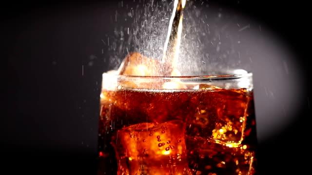 vídeos y material grabado en eventos de stock de cola con hielo y burbujas en cámara lenta de vidrio. - cola gaseosa