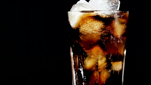 Cola with ice cubes and bubbles in glass, close-up, light moving. Cola drink, light in the dark. Cola with ice cubes and bubbles in glass, close-up, light moving. Cola drink, light in the dark. cola stock videos & royalty-free footage