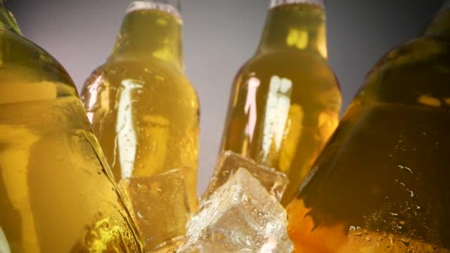 kalte bierflaschen mit eiswürfeln und wassertropfen. nahaufnahme dolly schuss - eimer stock-videos und b-roll-filmmaterial