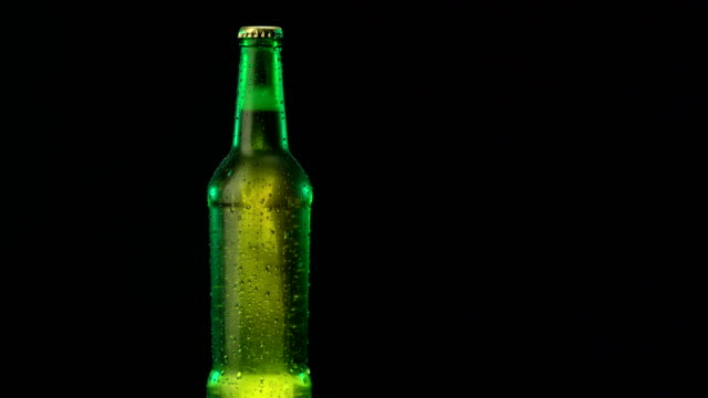 Cold beer in a green bottle rotating on a black background beer in green bottle condensation stock videos & royalty-free footage