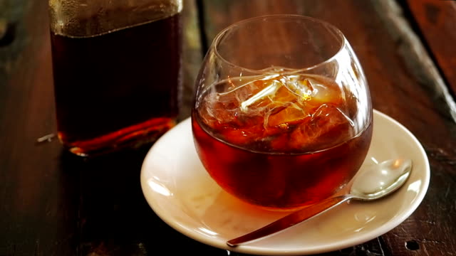 Cold brew coffee in a bottle with ice cubes in a glass tumbler on a wooden table from above. A bottle of cold brew coffee and ice in glass preparing Cold Brew drink. Man pours dutch coffee from a glass bottle into a glass cup with pieces of ice