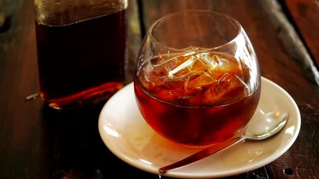 kall brygga kaffe i en flaska med isbitar i ett glas tumbler på ett träbord ovanifrån. en flaska kallt bryggkaffe och is i glas som förbereder kall brygd dryck. man häller holländsk kaffe från en glas flaska i en glaskopp med bitar av is - iskaffe bildbanksvideor och videomaterial från bakom kulisserna