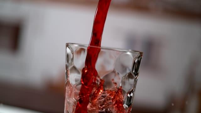 vídeos y material grabado en eventos de stock de jugo de cereza frío verter en vaso. movimiento súper lento - zumo
