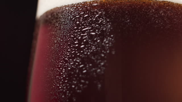 vídeos de stock e filmes b-roll de cold dark beer with foam in the glass, crane shot, close up. - lager