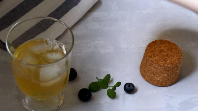 vidéos et rushes de thé fermenté maison froid et sain aux propriétés probiotiques naturelles. buvez avec de la glace dans un bol en verre sur un fond léger. position horizontale. position horizontale. - infusion pamplemousse