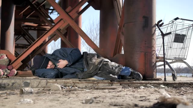 Cold homeless beggar sleeping under bridge Full length cold homeless beggar male in jacket sleeping under the bridge in fall, eyes covered with hat. Urban homeless person with no home staying overnight outside. Dolly shot homeless person stock videos & royalty-free footage