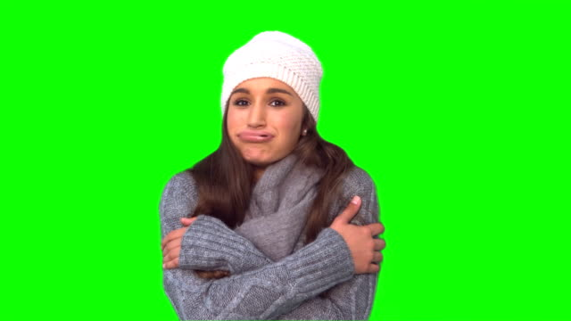 Cold pretty young woman shivering Cold pretty young woman shivering on green background shivering stock videos & royalty-free footage