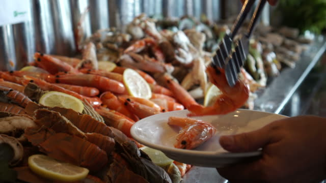 cold seafood buffet line hand taking poached shrimp 4k - buffet video stock e b–roll