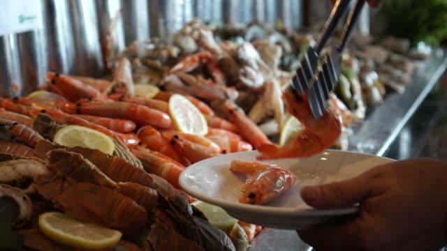 vídeos y material grabado en eventos de stock de buffet de mariscos fríos mano línea tomando camarones escalfados 4k - pescado y mariscos