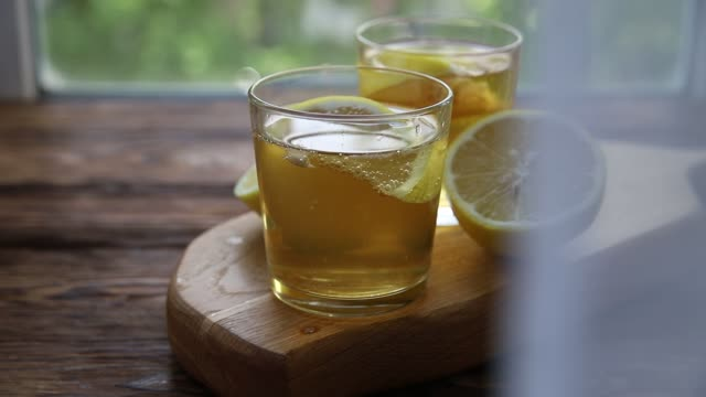Cold tea or fermented raw kombucha with lemon at summer day Cold tea or fermented raw kombucha with lemon at summer day. The tulle sways in the wind tulle netting stock videos & royalty-free footage