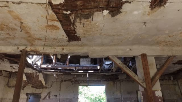 Collapsed roof of the total damaged domestic house indoor from natural disaster or catastrophe with big hole in the ceiling from heavy weather rain storm and water