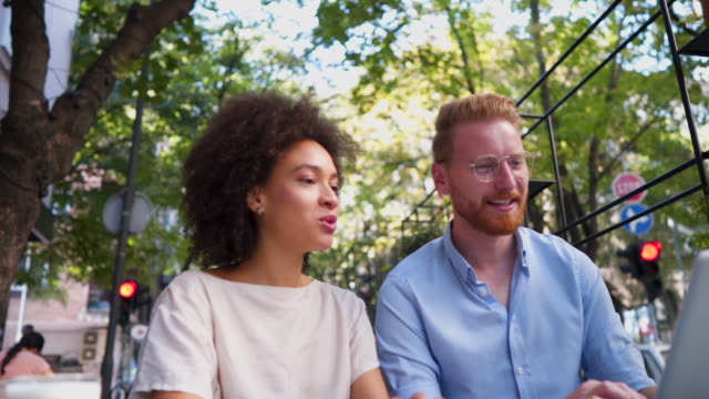 Colleague chit chat while working Mixed race businesswoman, and redhead caucasian man, working together in a coffee shop coworker stock videos & royalty-free footage