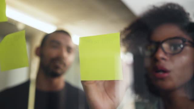 vídeos de stock, filmes e b-roll de colega que olha sua escrita nova da mulher de negócios na nota adesiva - post it