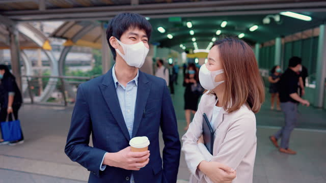 Colleague wear surgical mask while talking at capital city.