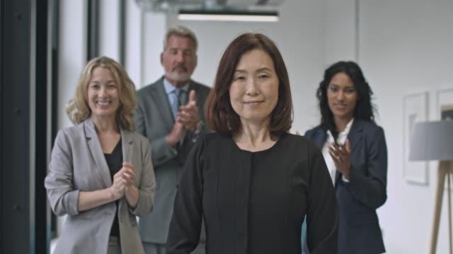 colleagues applauding japanese businesswoman - femminilità video stock e b–roll