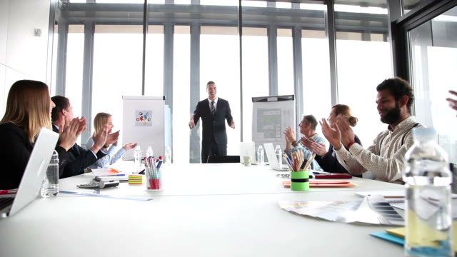 Colleagues applauding smiling businessmen during a meeting video