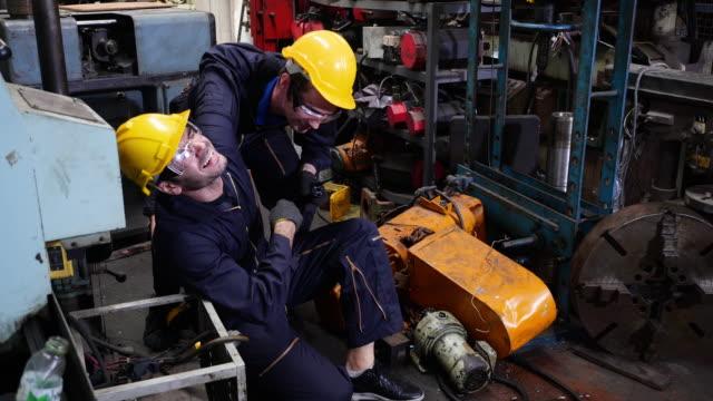 stockvideo's en b-roll-footage met collega's gaan werknemers helpen die gewond zijn geraakt door industriële machines. - tegenslag