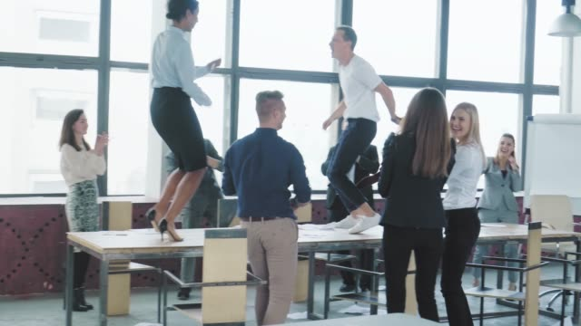 Colleagues celebrate the end of the work week, have fun dancing on the table. Success. Corporate party business team. Modern trendy office interior. Managers entertainment video
