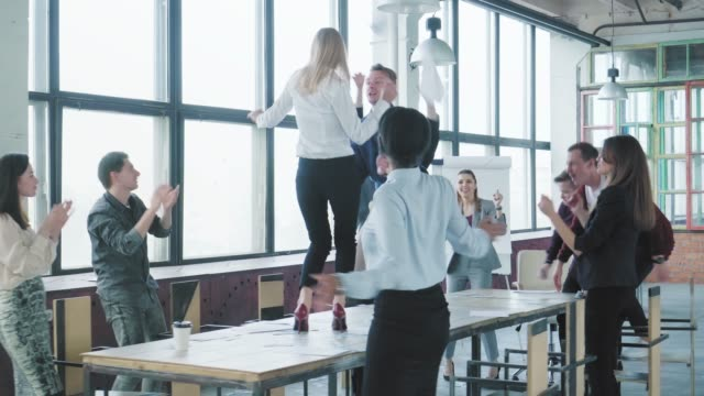 Colleagues celebrate the end of the work week, have fun dancing on the table. Managers rejoice at success and scatter money and documents. Corporate party business team. Trendy office interior video