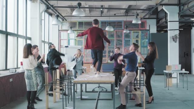 Kollegen feiern das Ende der Arbeitswoche, haben Spaß am Tanzen auf dem Tisch und werfen Papier auf. Erfolg. Corporate Party Business Team. Modernes trendiges Büro-Interieur. Mitarbeiter Unterhaltung – Video