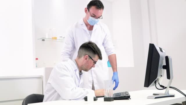 kollegen diskutieren laborarbeit an neuen medikamenten und viren - überprüfung stock-videos und b-roll-filmmaterial