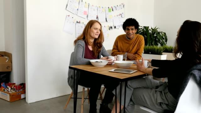 vídeos de stock e filmes b-roll de colleagues discussing at table in cafeteria - cantina