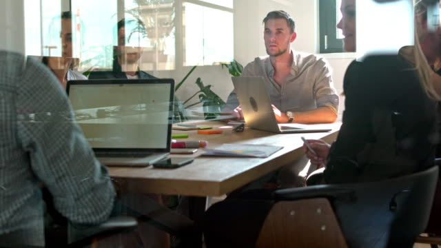 Colleagues discussing during meeting in office Web designers looking at colleague explaining during meeting in office. Male and female business professionals are sitting at conference table. They are wearing smart casuals. it professional stock videos & royalty-free footage