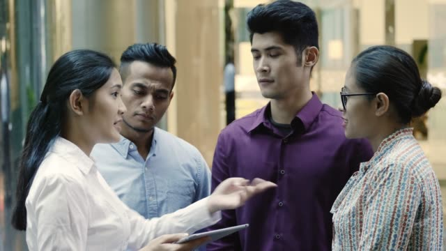 colleagues discussing over digital tablet at office - kuala lumpur video stock e b–roll