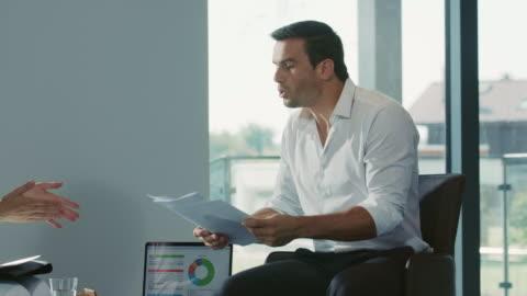 vídeos y material grabado en eventos de stock de colegas discutiendo cuestiones de trabajo. hombre de negocios tirando papel. - parte del cuerpo humano