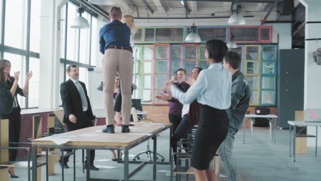 同僚は、近代的なトレンディなオフィスでテーブルの上で楽しく踊り、成功を祝います。コーポレートパーティービジネスチーム。支配人はテーブルから飛び降りる。コワーキング ビデオ