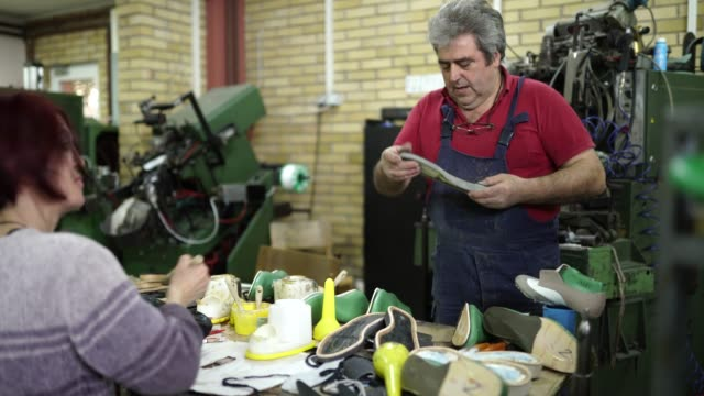 Colleagues in shoe factory working together