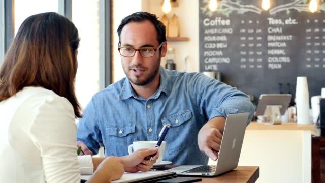 colleagues meet at coffee shop to discuss business ideas - praca w sektorze handlowym filmów i materiałów b-roll