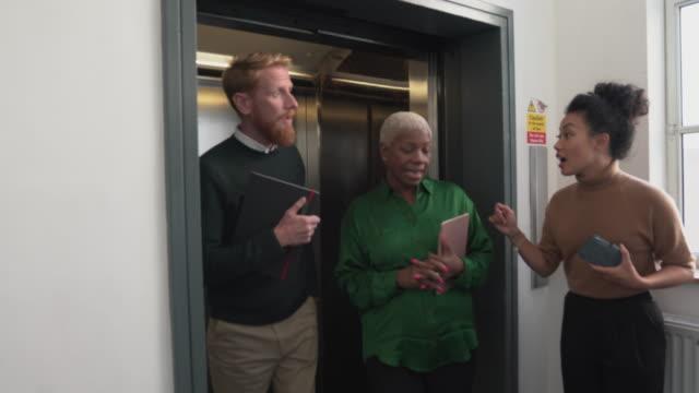 동료들은 엘리베이터에서 만나 매니저의 관심을 끌기 위해 경쟁합니다. - black friday 스톡 비디오 및 b-롤 화면