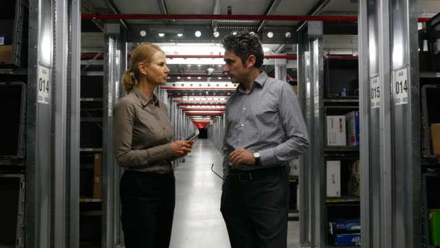 Colleagues Shaking Hands And Discussing By Shelves video