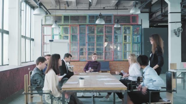 同僚は大きなテーブルに座り、近代的なトレンディなオフィスで会議を開きます。マネージャーはオフィスの椅子でスイングします。起動します。ビジネスチーム。コワーキング。オフィス� ビデオ
