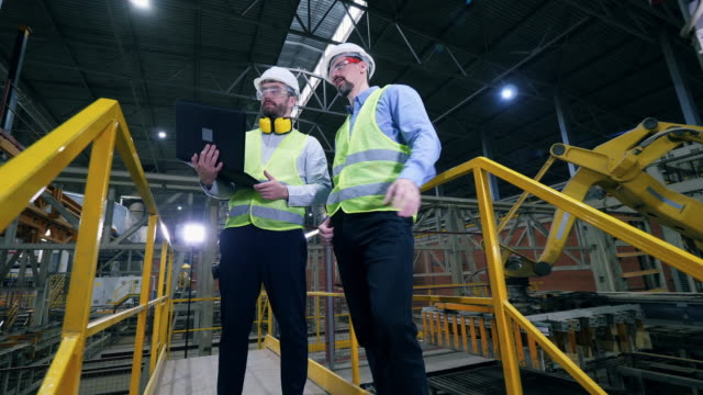 Colleagues stand in a factory facility, checking the work of factory machines.
