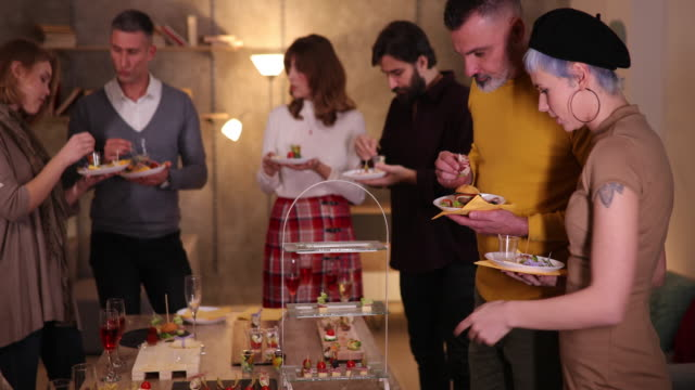 Colleagues taking food from table during networking event in modern office