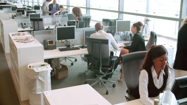 Colleagues talking at a desk in a busy open plan office