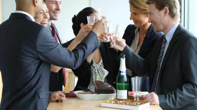 colleagues toasting champagne flutes during party - office party stock videos and b-roll footage