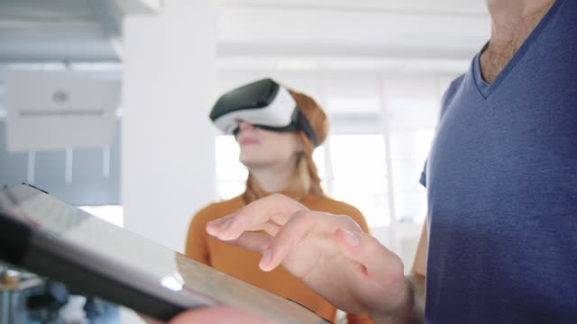 Colleagues using digital tablet and VR glasses