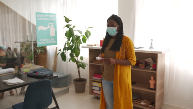 Colleagues with protective masks measuring body temperature in office video