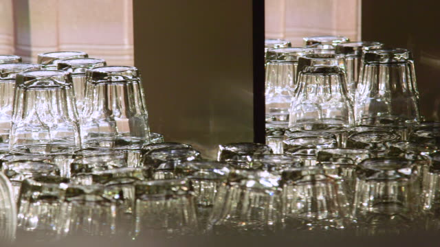 collection of glassware stacked neatly behind bar during special event - bicchiere vuoto video stock e b–roll