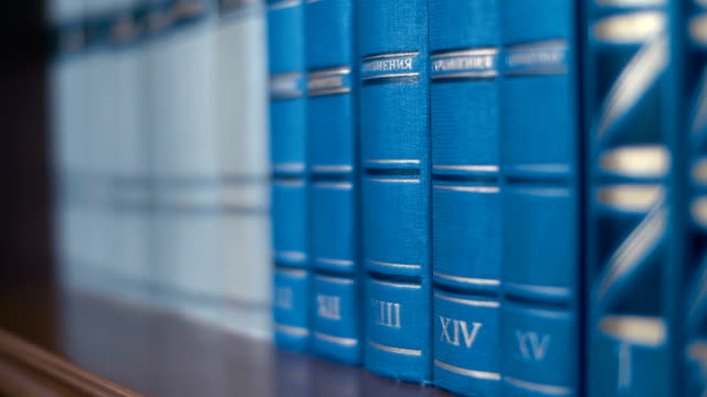Collection of volumes of books of blue color by different writers on a bookshelf Collection of volumes of books of blue color by different writers on a wooden bookshelf. Closeup. Follow focus. Shallow depth of field textbook stock videos & royalty-free footage