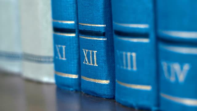 samling av volymer av bokar av blått färgar vid olika författare på en bokhylla - lagbok bildbanksvideor och videomaterial från bakom kulisserna