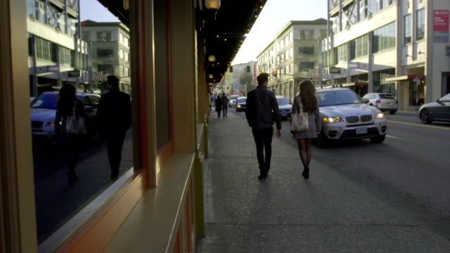 College couple stroll into distance of urban street video