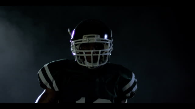 College football player stares through mist to camera